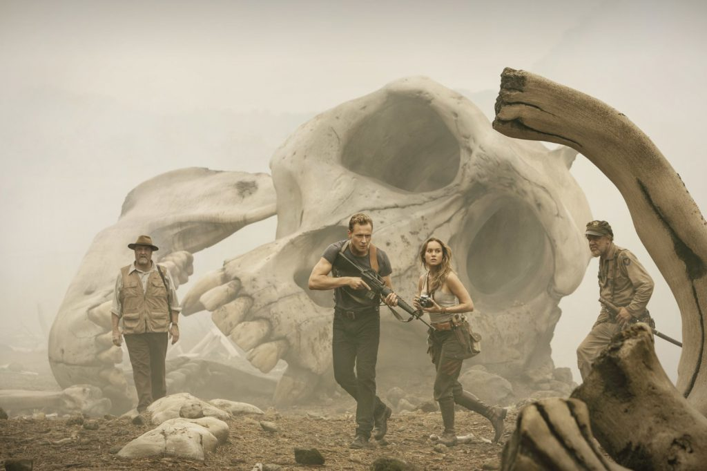 John Goodman, Tom Hiddleston, Brie Larson, and John C Reilly in front of a giant gorilla skull