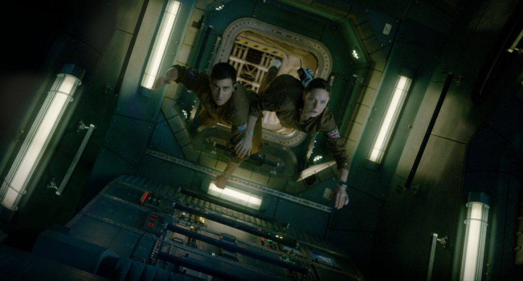 Jake Gyllenhaal and Rebecca Ferguson as two astronauts floating through a corridor in the International Space Station