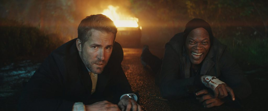 Ryan Reynolds (l) and Samuel L. Jackson (r) are lying on the ground, propped up on their elbows. A van is on fire behind them.