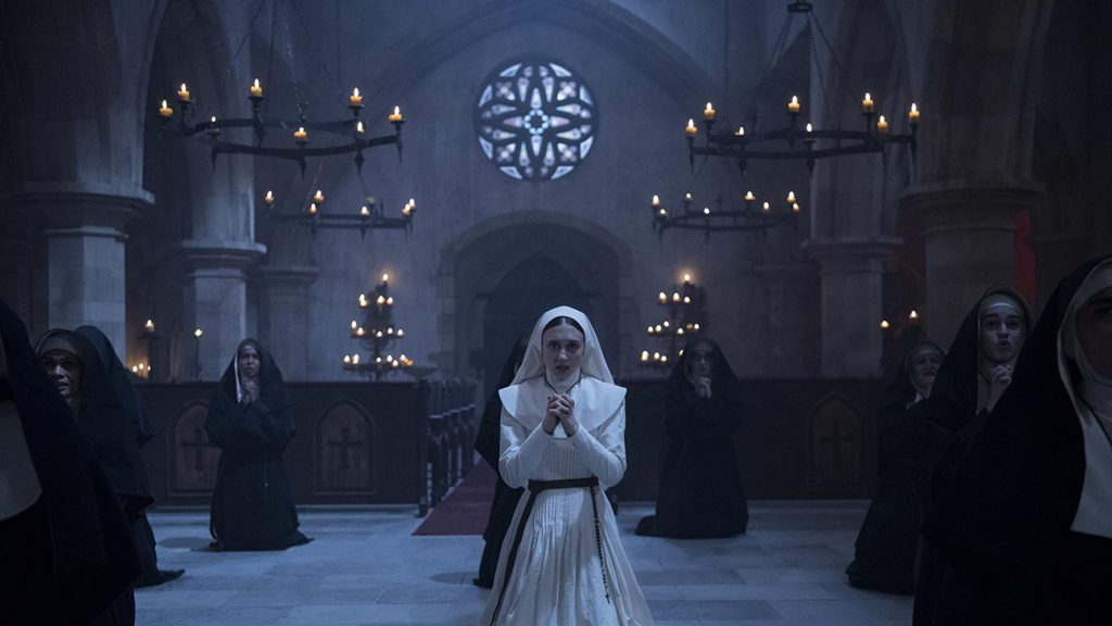 "Taissa Farmiga as Sister Irene in ""The Nun"" prays with other nuns in a chapel."