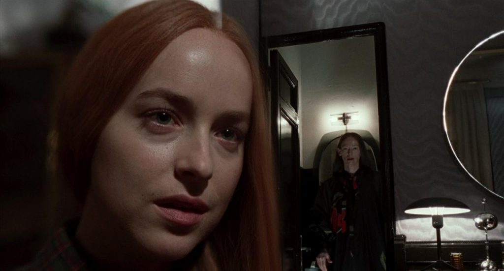 A shot from the movie Suspiria. Dakota Johnson is close up on the left side, while a mirror behind her shows Tilda Swinton ont he right side of the photo